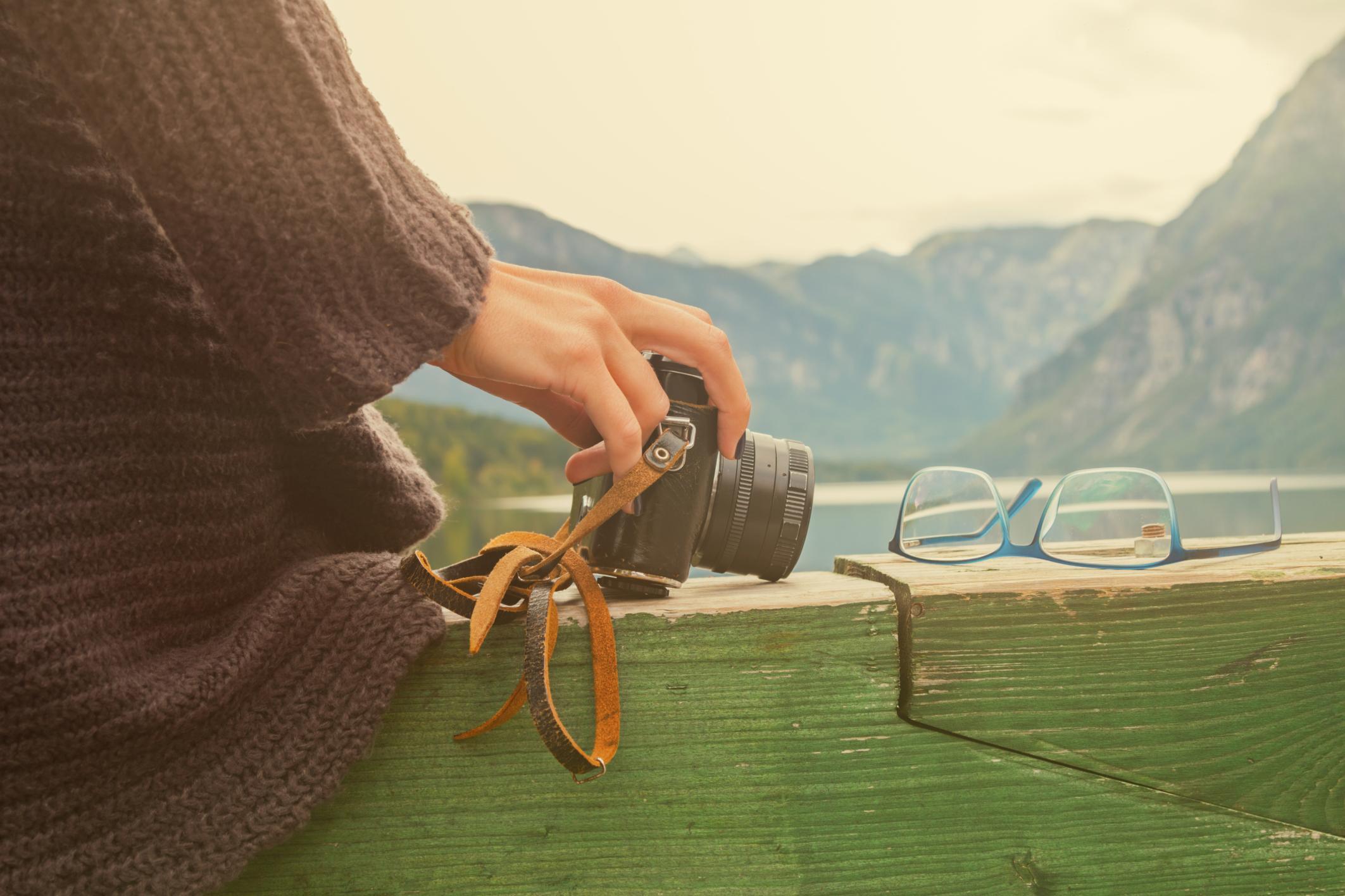 Primer plano cámara de fotos, gafas y mano de mujer