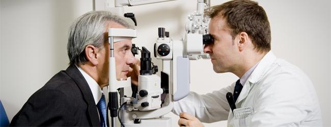 Oftalmólogo revisa la vista a un hombre en una lámpara de hendidura