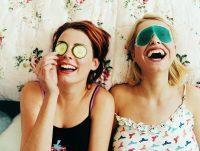 Chica morena y chica rubia riéndose con máscaras en los ojos