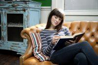 Mujer morena con flequillo leyendo en un sillón