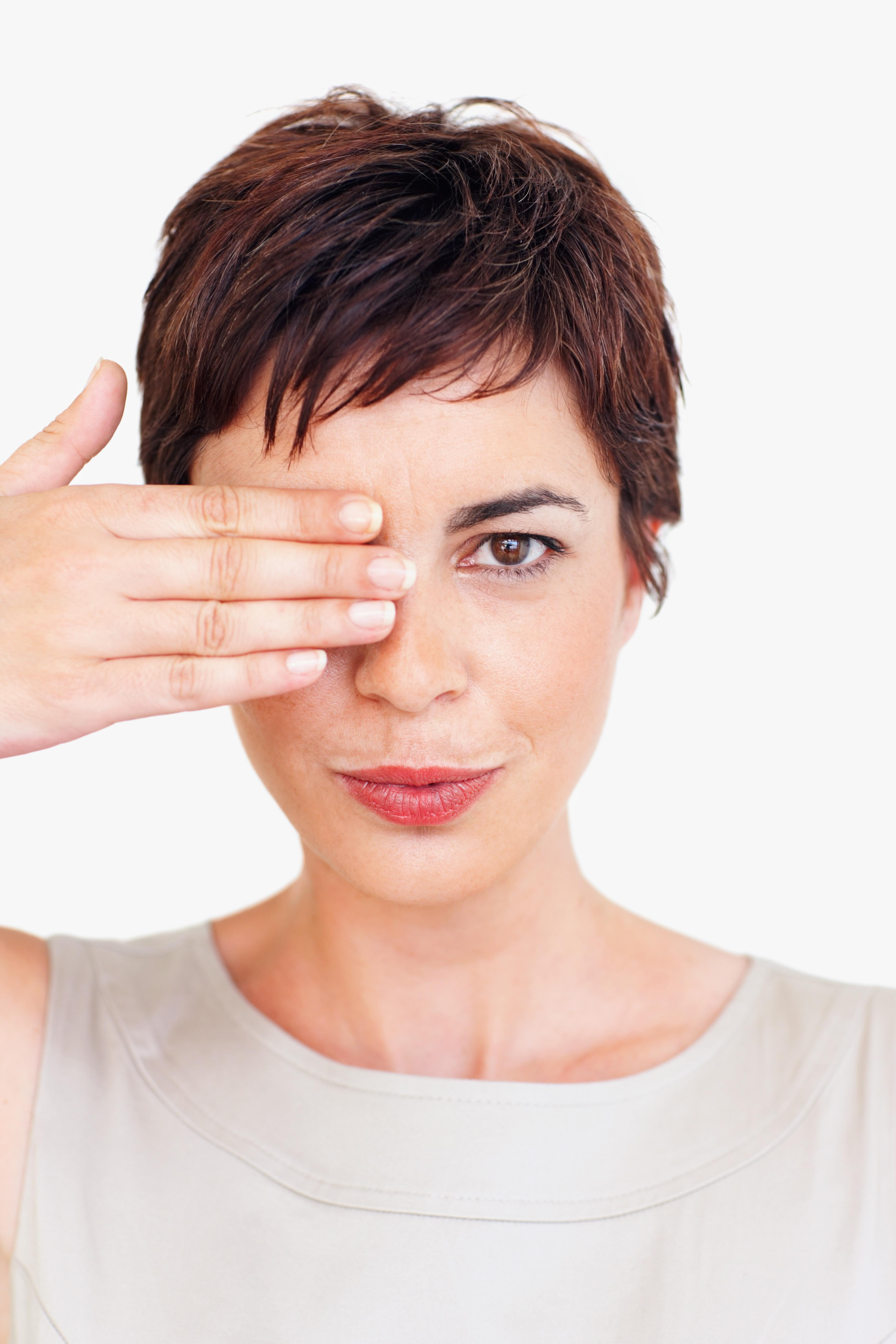 Mujer con camiseta beige tapándose un ojo