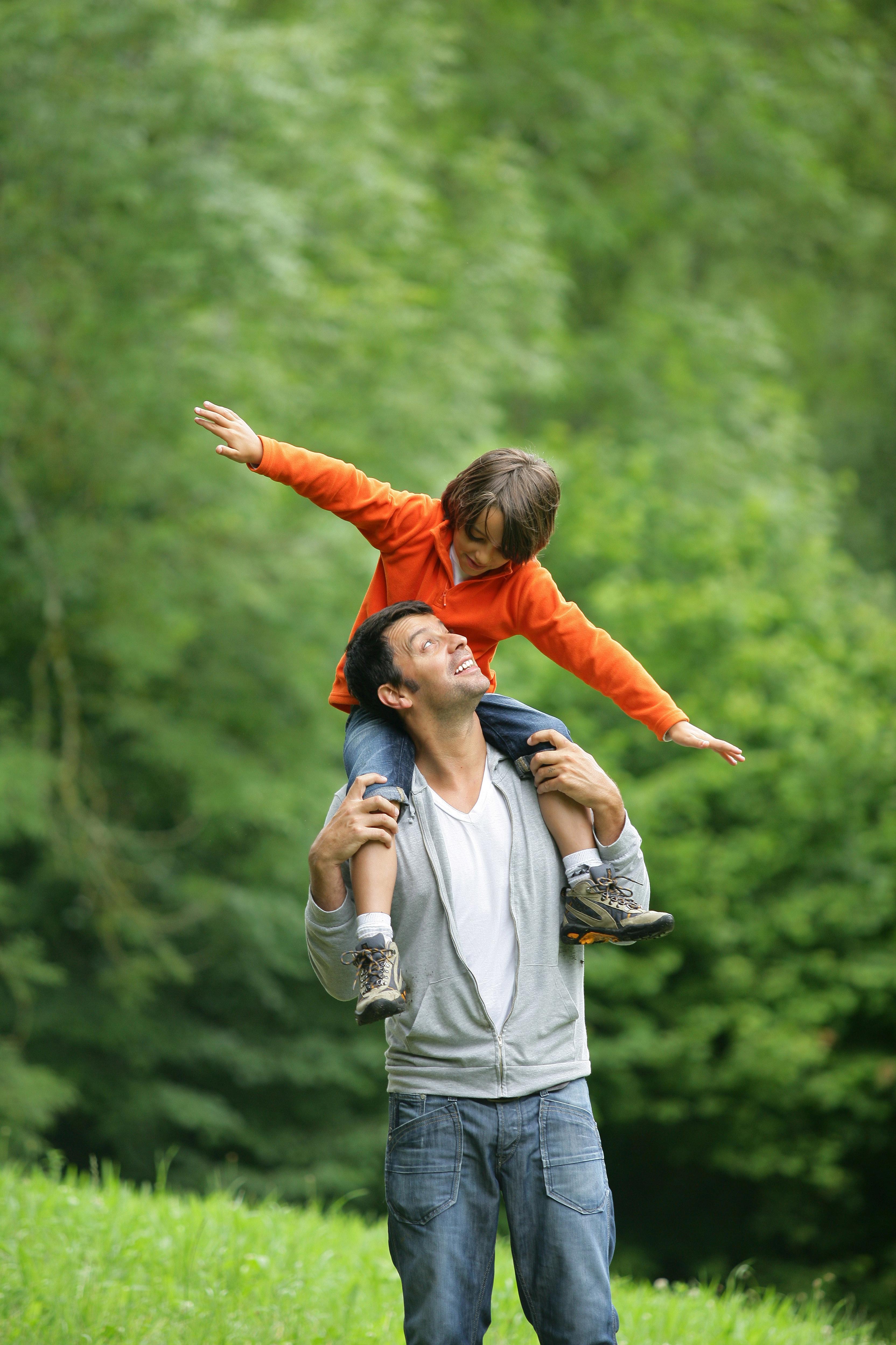 Hombre con chaqueta gris lleva sobre los hombros a niño