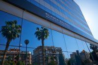 Fachada Clínica Baviera Alicante con reflejo de palmeras