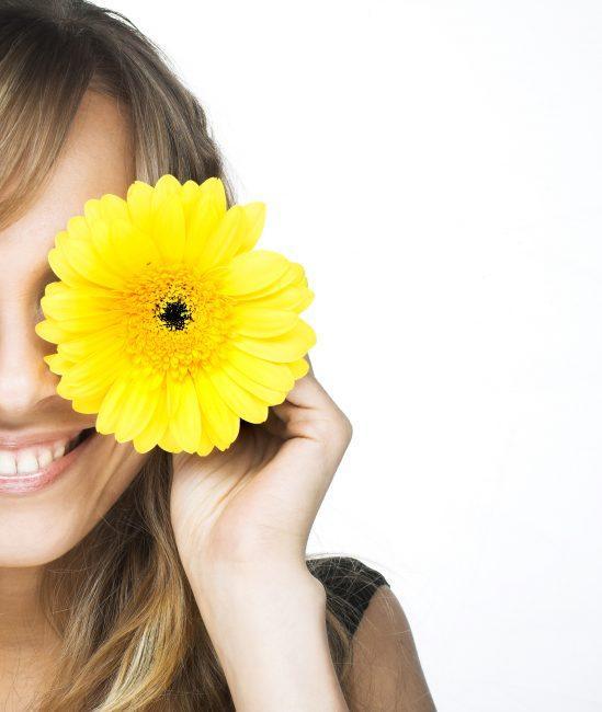 Mujer rubia se pone una flor amarilla en un ojo