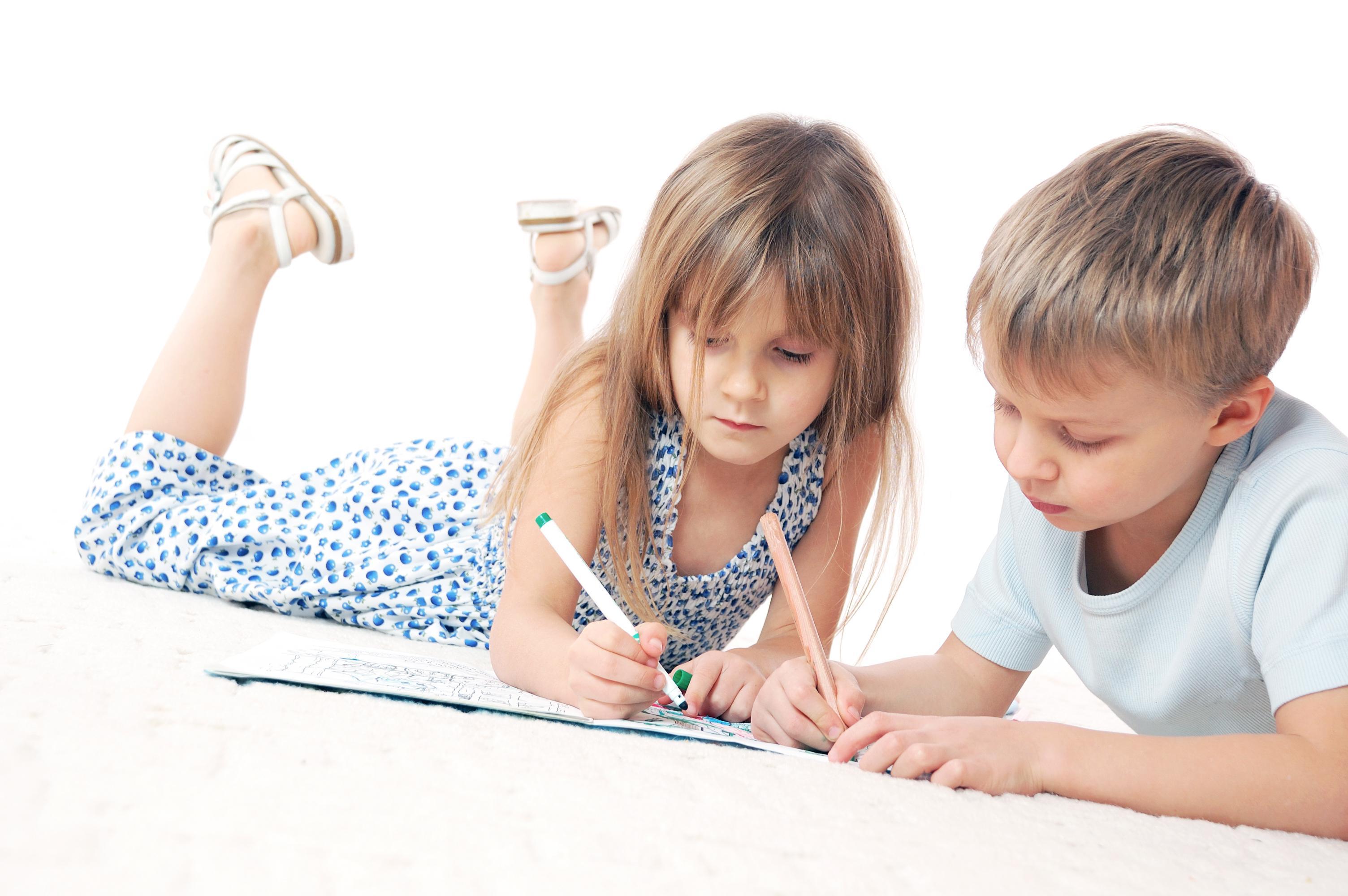 Niño y niña dibujando tumbados en el  suelo