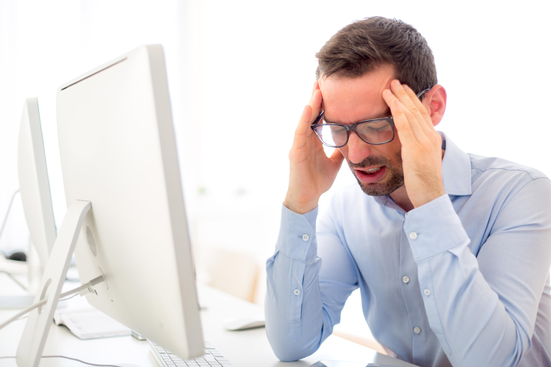 Hombre con gafas y camisa azul frotándose las sienes