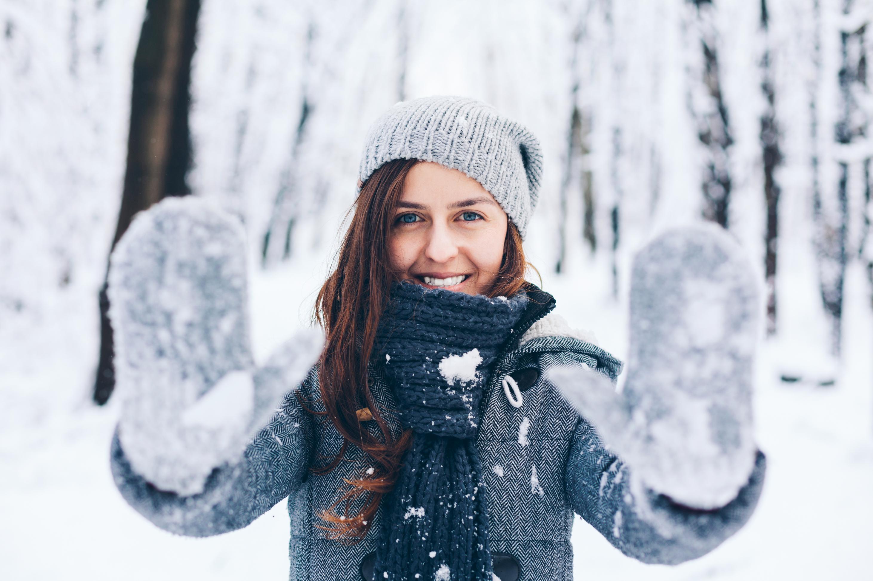 Mujer con gorro y guantes jugando con la nieve