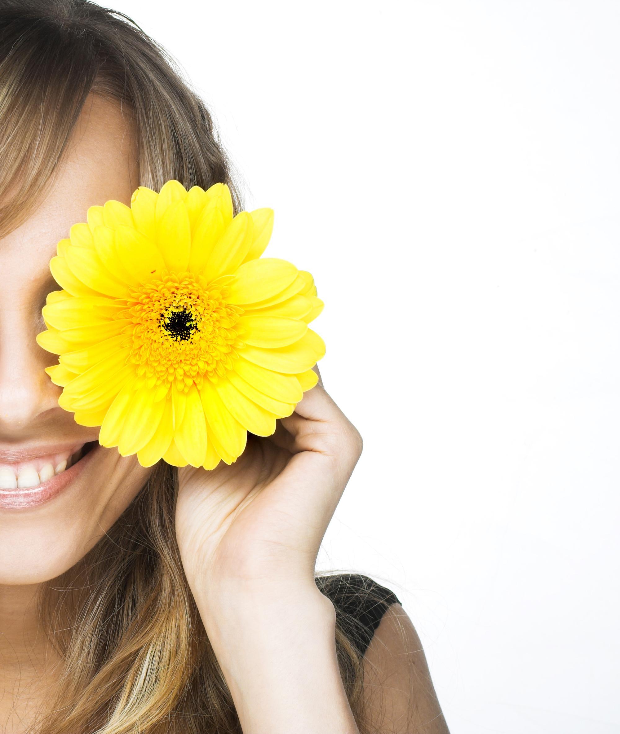 Mujer con camiseta negra tapándose un ojo con una margarita amarilla
