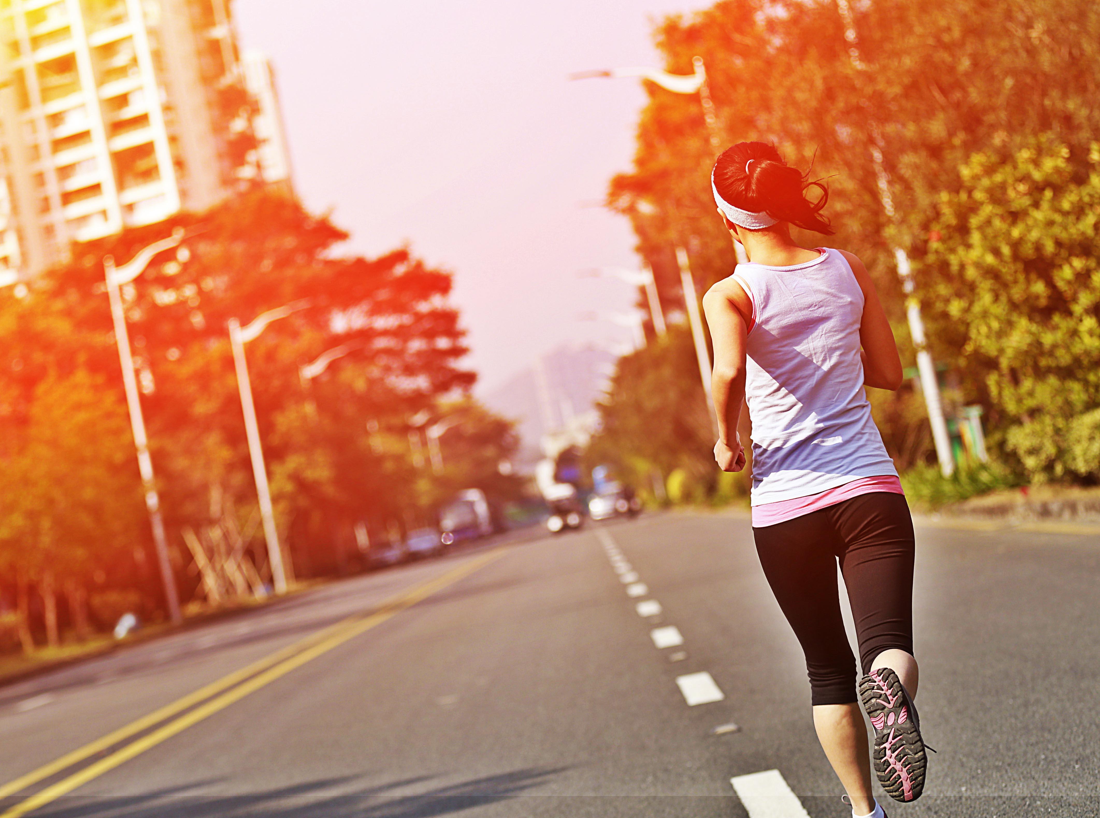 Mujer corriendo por una carretera vacía