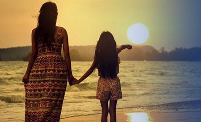 Niña y mujer observando una puesta de sol