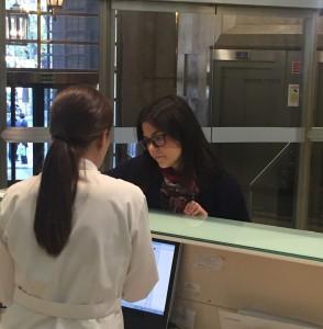 Paciente hablando con auxiliar de clínica en la recepción