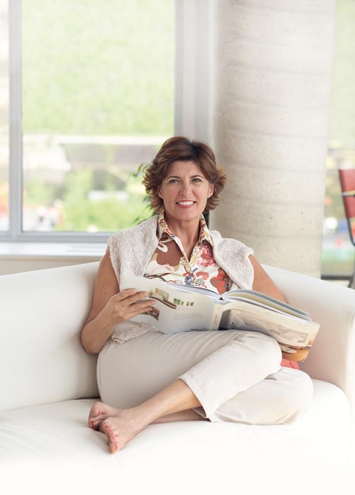 Señora castaña con media melena lee un libro en un sillón