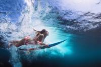 Mujer con tabla de surf en el mar