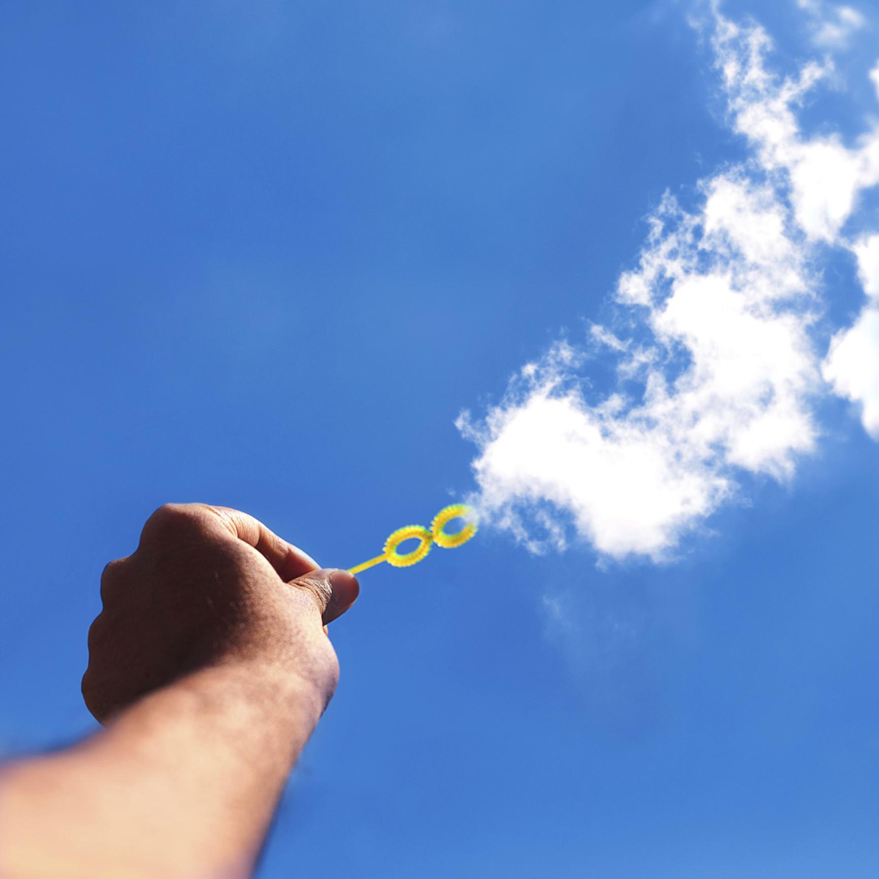 Ilusión óptica mano haciendo pompas con nubes