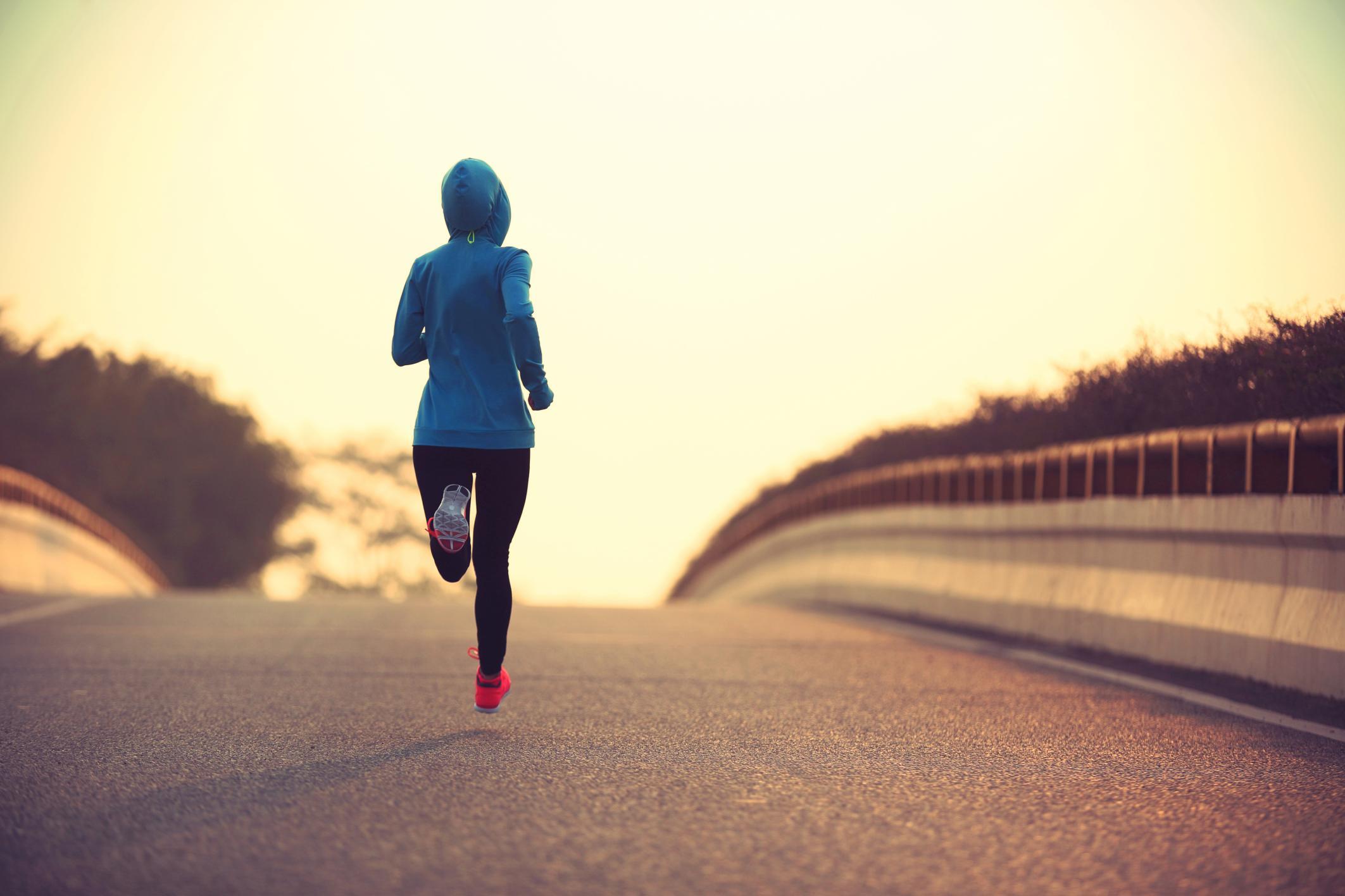 Mujer con sudadera azul y zapatillas rosas corriendo por una carretera