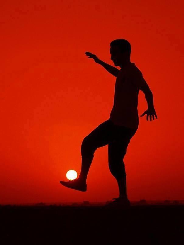 Ilusión óptica hombre jugando al fútbol con el sol