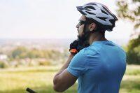 Ciclista con camiseta azul poniéndose el casco