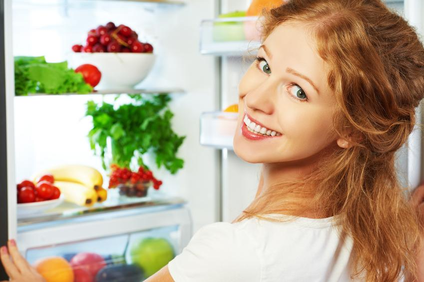 Mujer pelirroja abriendo un frigorífico