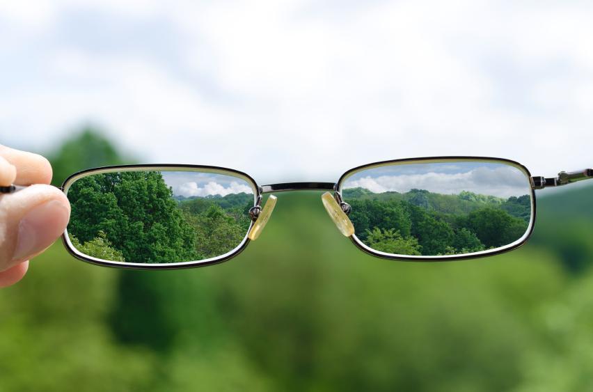 Gafas sobre fondo de paisaje verde