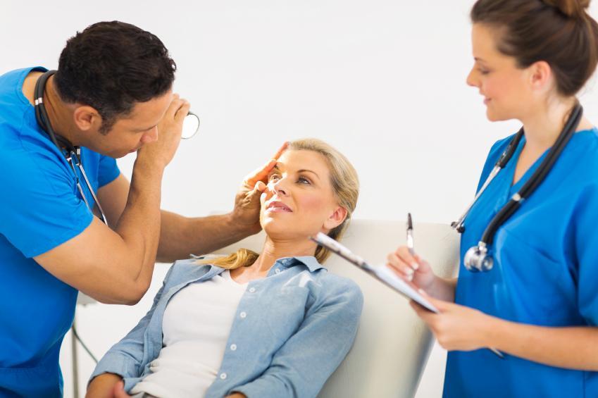 Oftalmólogo y enfermera revisando la vista a una mujer