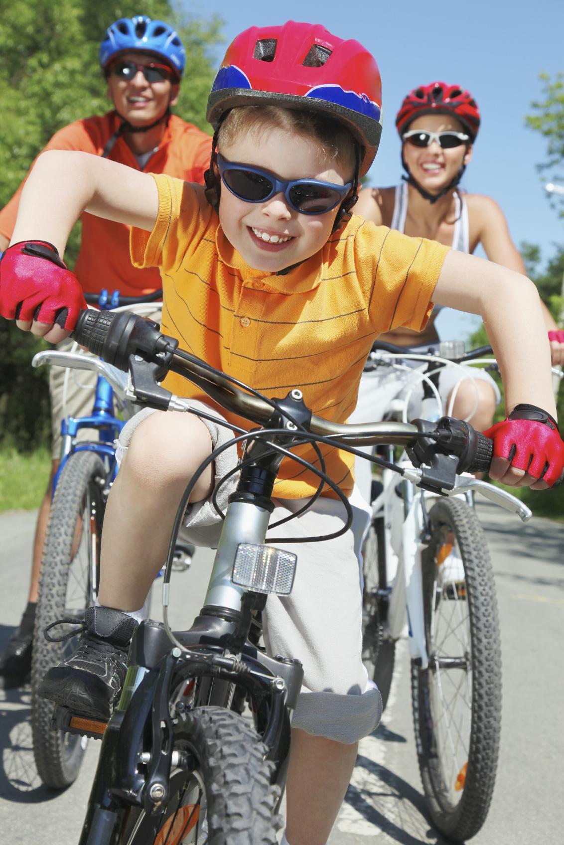 Niño montando en bicicleta con sus padres