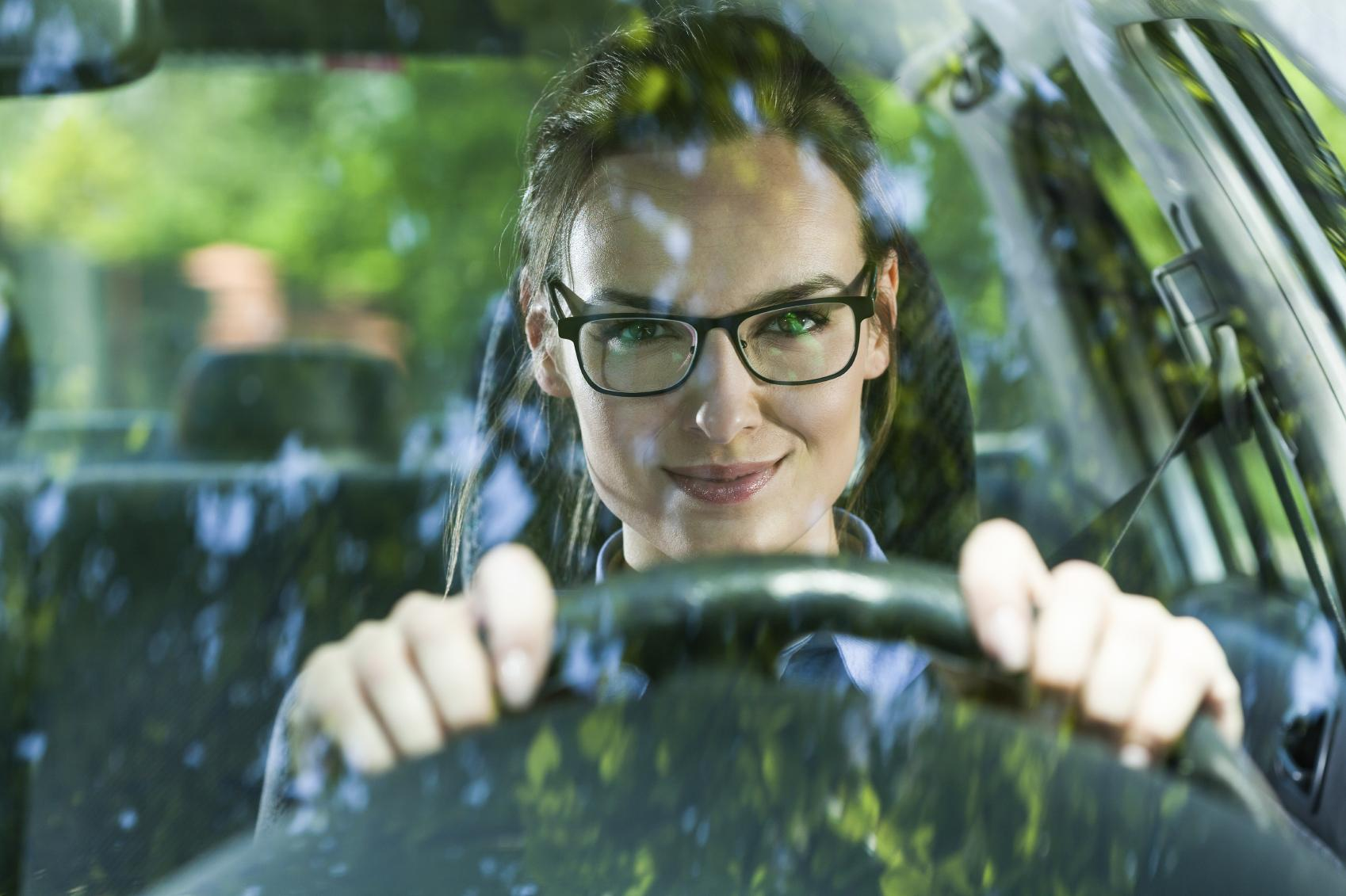Mujer con gafas conduciendo un coche