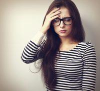 Mujer con jeresey a rayas y gafas se toca la cabeza