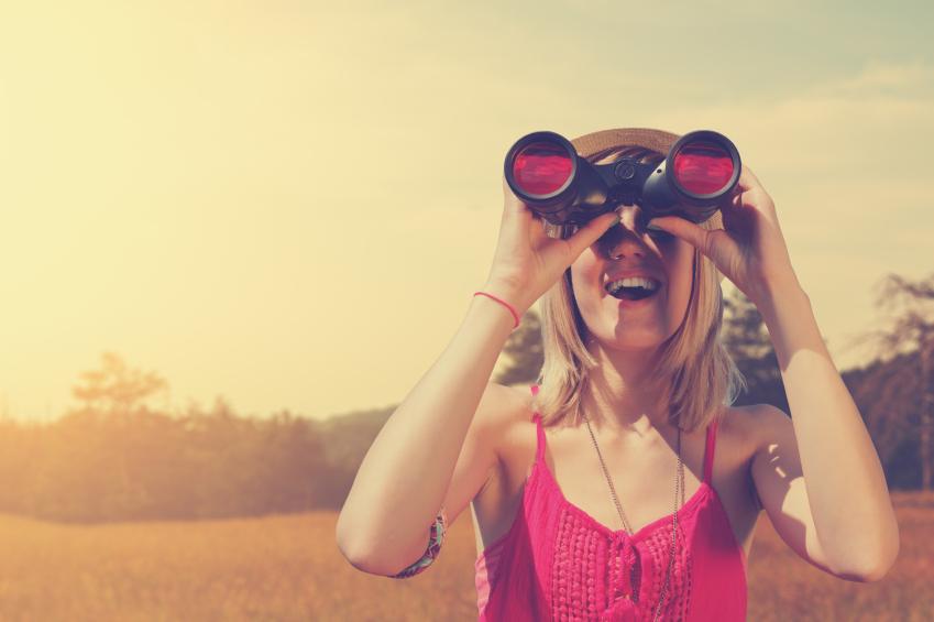 Chica con camiseta roja mirando por unos prismáticos