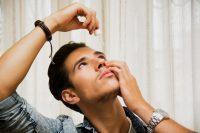 Hombre con pulsera y reloj echándose un colirio