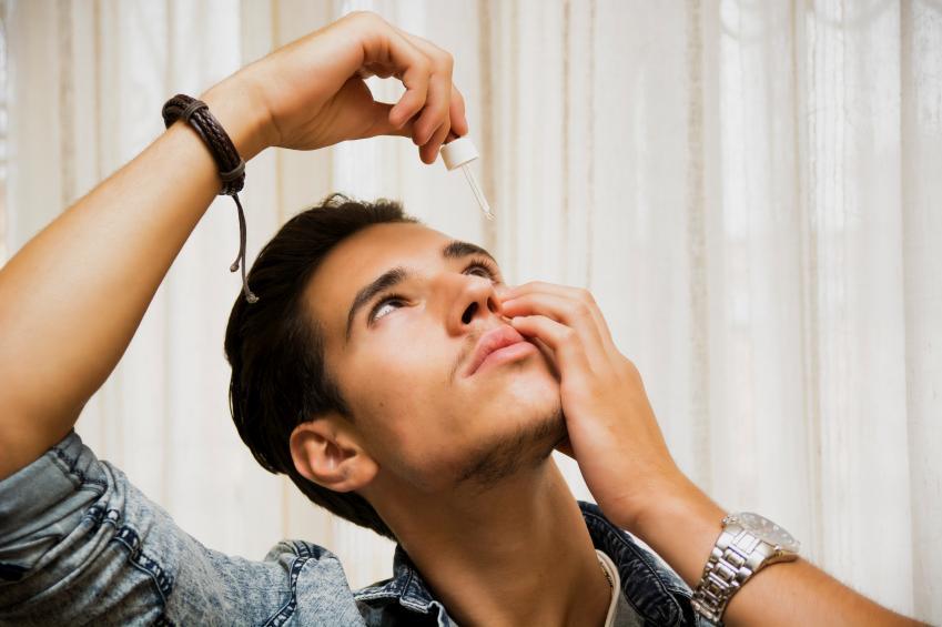 Hombre joven echándose gotas en los ojos