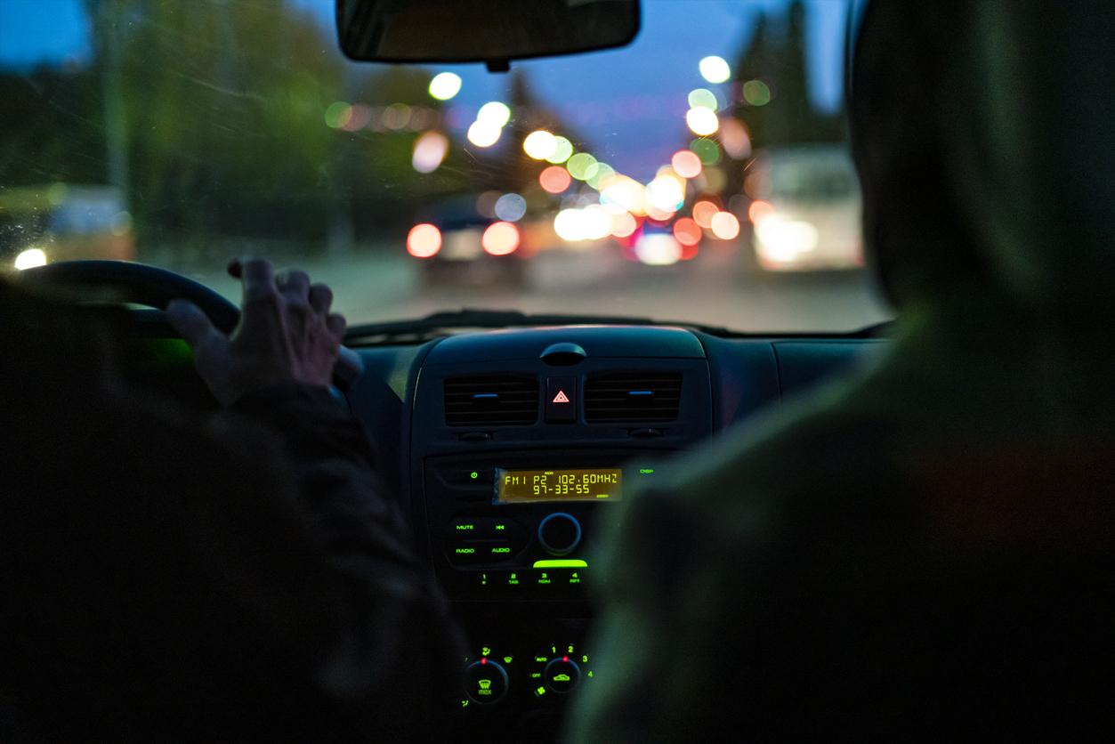 Hombre conduciendo un coche por la noche