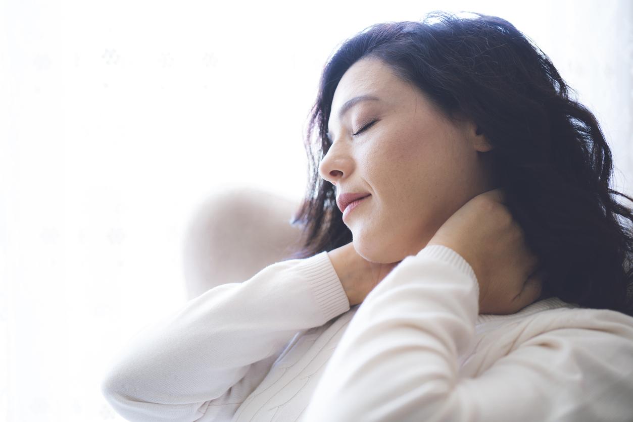Mujer con pelo negro largo se frota el cuello