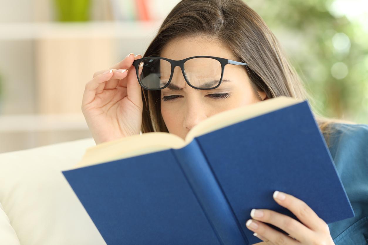 Mujer se levanta las gafas para leer un libro azul