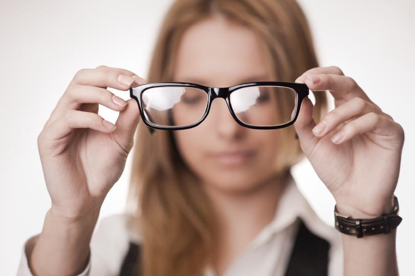 Mujer con camisa blanca mirando unas gafas negras