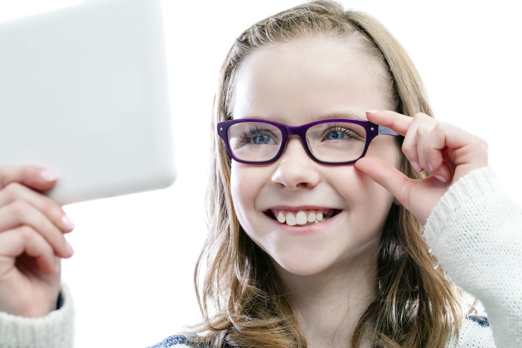 Niña rubia probándose unas gafas moradas