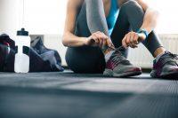 Mujer atándose los cordones de unas zapatillas de deporte