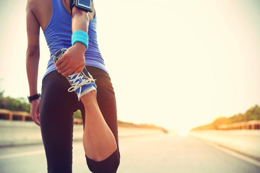Mujer deportista estirando antes de correr