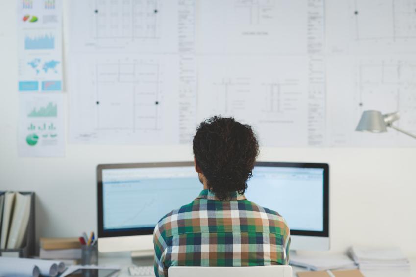 Hombre con camisa a cuadros trabajando frente a un ordenador