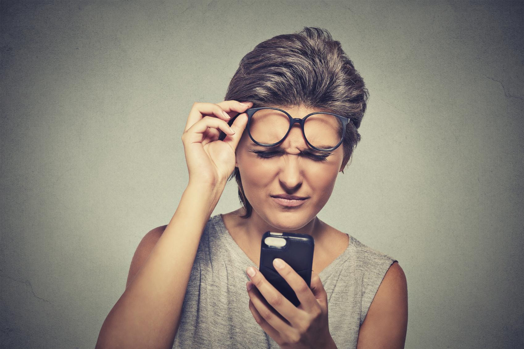 Mujer mirando un móvil y levantándose las gafas para ver