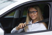 Mujer con gafas y camisa blanca poniéndose el cinturón del coche
