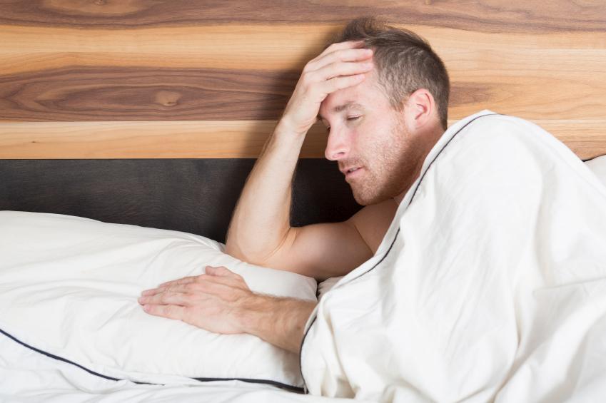 Hombre en la cama con dolor de cabeza nocturno