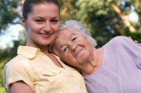 Mujer joven con camiseta amarilla y mujer mayor con jersey lila abrazándose