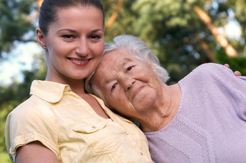 Mujer joven con camisa amarilla abrazando a una mujer mayor