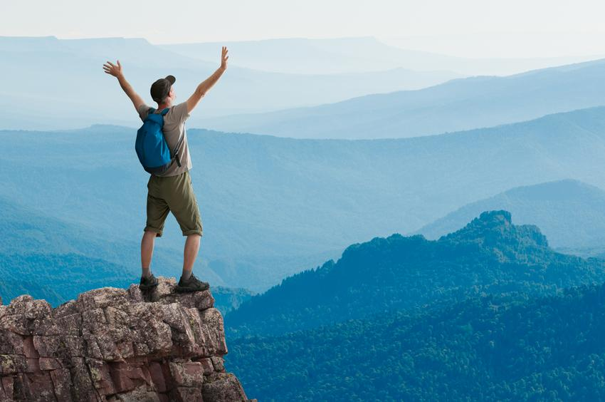 Hombre con mochila azul en un cañón