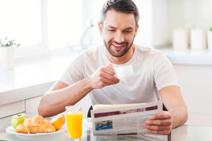 Hombre desayunando y leyendo un periódico