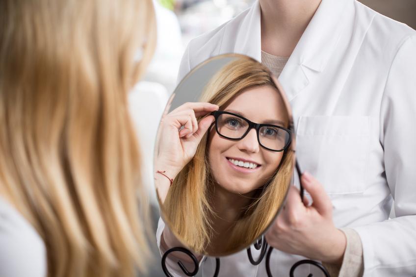 Mujer rubia probándose tipos de gafas frente al espejo