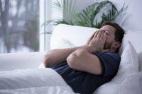 Hombre con camiseta gris en cama con sábanas blancas