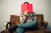 Hombre leyendo un libro rojo