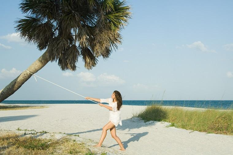 Mujer tira de una cuerda atada a una palmera
