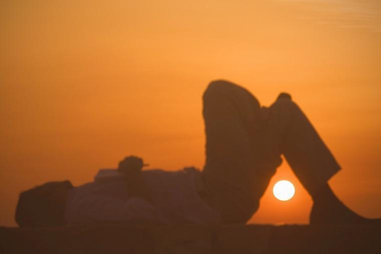 Hombre tumbado mirando el sol